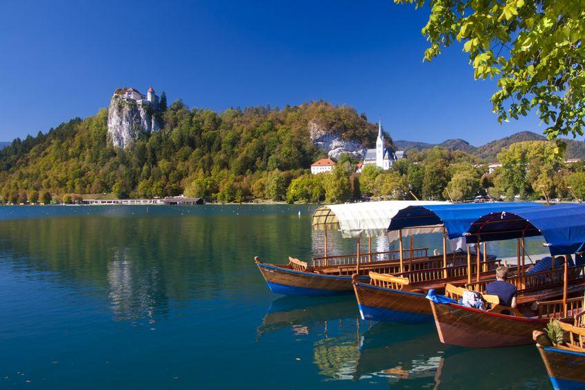 Hagyományos, fából készült csónakok, háttérben a bledi vár